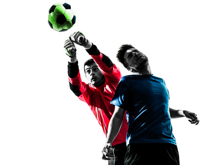 two caucasian soccer player goalkeeper men punching heading ball competition in silhouette isolated white background Banco de Imagens