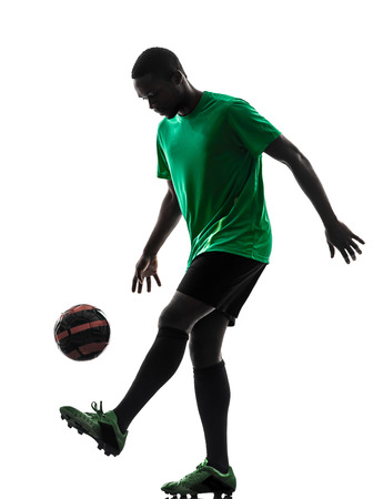 juggling: one african man soccer player green jersey juggling in silhouette on white background Stock Photo