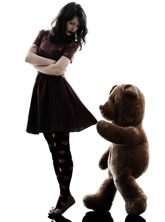one caucasian strange young woman and vicious teddy bear in silhouette white background photo