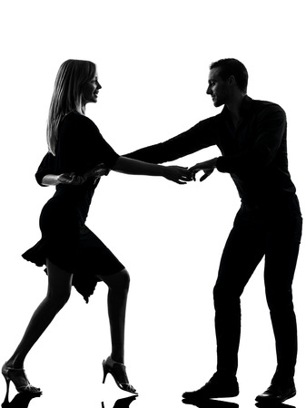 people dancing: one caucasian couple woman man dancing dancers salsa rock in silhouette studio isolated on white background Stock Photo