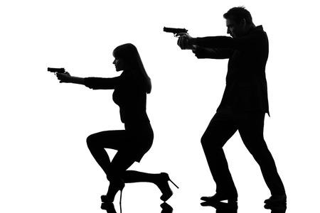 흰색 배경에 고립 된 실루엣 스튜디오에서 총을 가진 한 백인 남자 형사 비밀 요원의 범죄