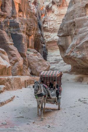 siq: Petra, Jordan - May 11, 2013: people in horse cart at the Siq path in Nabatean Petra Jordan Editorial