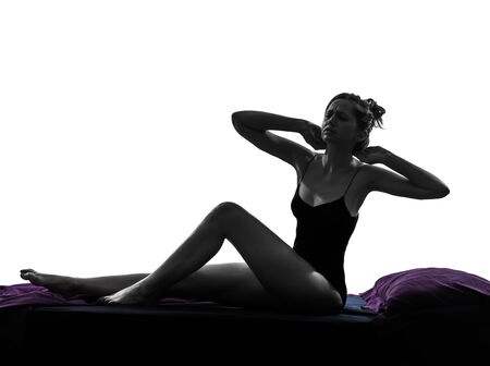 one woman waking up stretching backache sitting in bed silhouette studio on white background photo