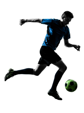 juggling: one caucasian soccer player man juggling ball in silhouette isolated white background
