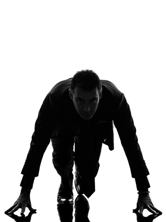 cut the competition: one caucasian business man on starting block in silhouette  on white background