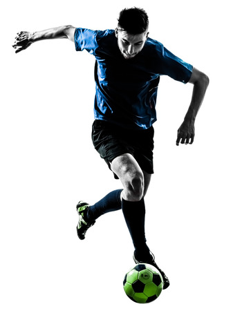 kicking ball: one caucasian soccer player man juggling ball in silhouette isolated white background