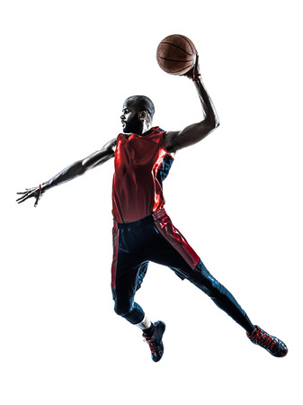 a basketball player: one african man basketball player jumping dunking in silhouette isolated white background