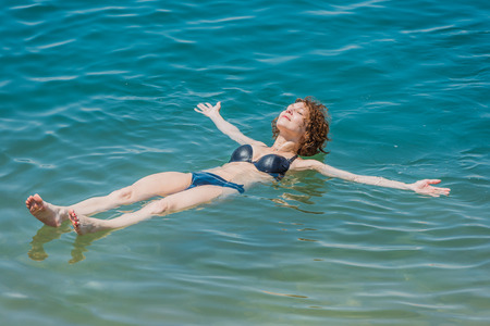 one woman: one woman floating in dead sea, jordan