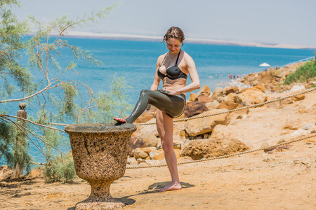one caucasian woman applying dead sea mud body care treatment in jordan photo