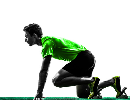 gente corriendo: un hombre cauc�sico joven corredor velocista en bloques de salida estudio de la silueta sobre fondo blanco Foto de archivo