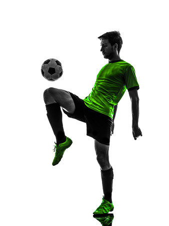 juggling: one soccer football player young man juggling in silhouette studio on white background Stock Photo