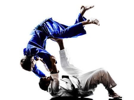 judo: dos judokas combatientes que luchan los hombres en siluetas en el fondo blanco