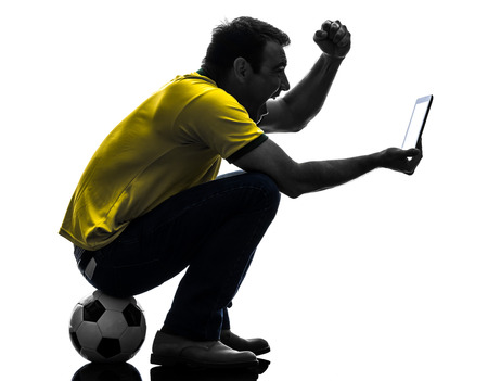 watching football: one  man holding digital tablet in silhouette on white background Stock Photo