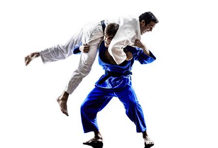 judo: dos judokas combatientes que luchan los hombres en siluetas en blanco Foto de archivo