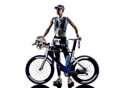 'cycles: man triathlon iron man athlete standing with all his equipment in silhouettes on white