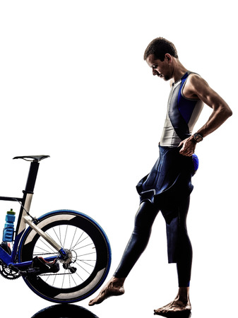 man triathlon iron man athlete standing with all his equipment in silhouettes on white background photo