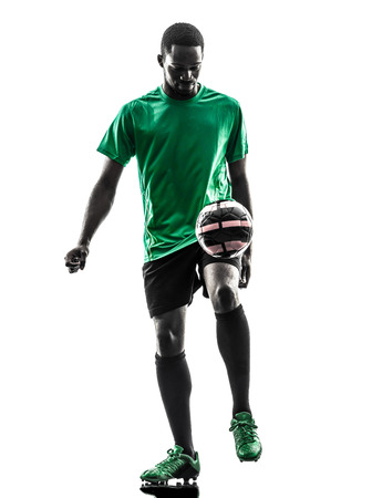juggling: one african man soccer player green jersey juggling in silhouette on white  Stock Photo