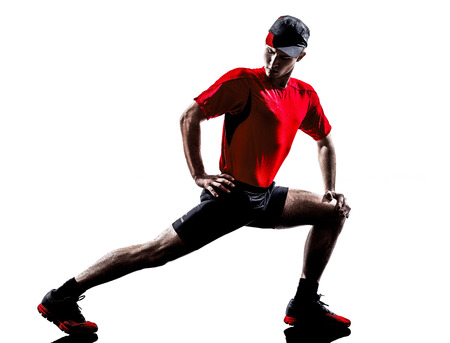 lunges: one young man runners joggers stretching warming up in silhouettes isolated on white background