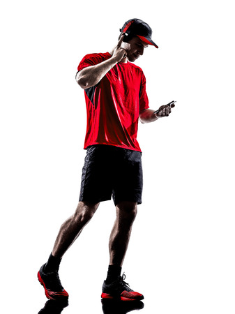 one young man runners joggers using smartphones headphones in silhouettes isolated on white background photo