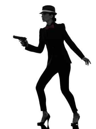 one stylish  woman in suit holding gun in silhouette on white background photo
