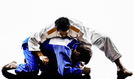 arte marcial: dos judokas combatientes que luchan los hombres en siluetas en el fondo blanco