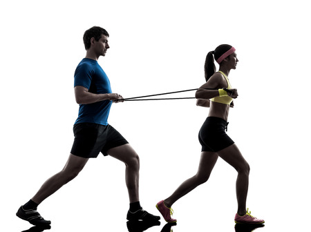 rubber band: one woman exercising resistance rubber band fitness workout with man coach in silhouette on white background