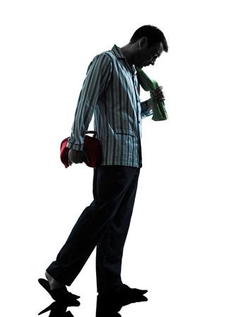 tired man: one man in pajamas sleepy  tired silhouettes on white background Stock Photo