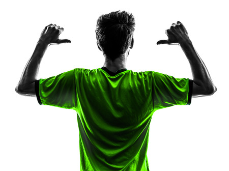 one soccer football player young man rear view portrait pointing in silhouette studio on white background photo
