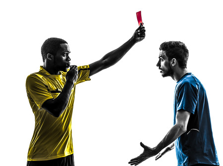 two men soccer player and referee showing red card in silhouette on white background photo