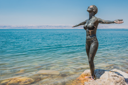 one woman: one  woman applying Dead Sea mud body care treatment in Jordan