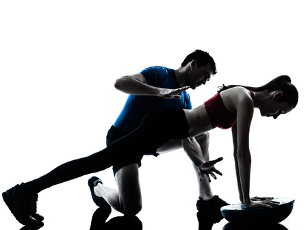 personal: personal trainer man coach and woman exercising abdominals push ups on bosu silhouette studio isolated on white background