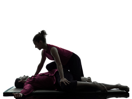 shiatsu: one man and woman performing thai massage in silhouette studio on white background