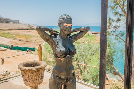 one  woman applying Dead Sea mud body care treatment in Jordan photo
