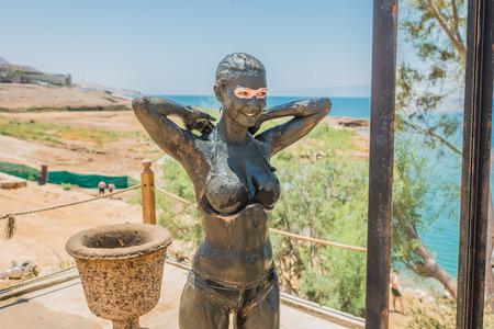 dead woman: one  woman applying Dead Sea mud body care treatment in Jordan