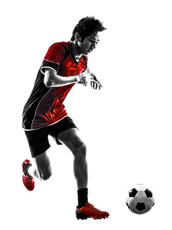 dribbling: one asian soccer player young man dribbling in silhouette isolated white  Stock Photo
