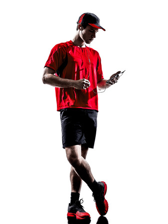 one young man runner jogger using smartphones headphones in silhouette isolated on white  photo