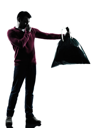 dumping: man dumping smelly garbage bag in silhouettes on white background