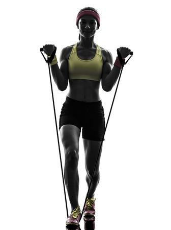 una mujer el ejercicio de las bandas de resistencia del entrenamiento de la aptitud en la silueta en el fondo blanco photo