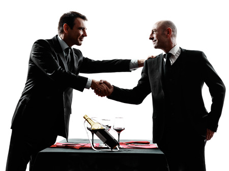 handshakes: two businessmen dinning handshaking in silhouettes on white background