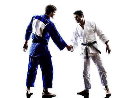 manos estrechadas: dos judokas combatientes que luchan los hombres del apret�n de manos en la silueta en el fondo blanco