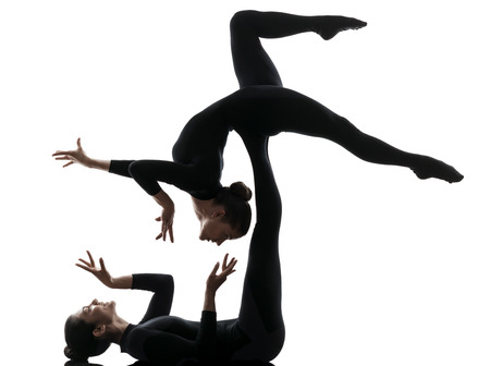 gymnastics silhouette: two women contortionist practicing gymnastic yoga in silhouette on white background Stock Photo