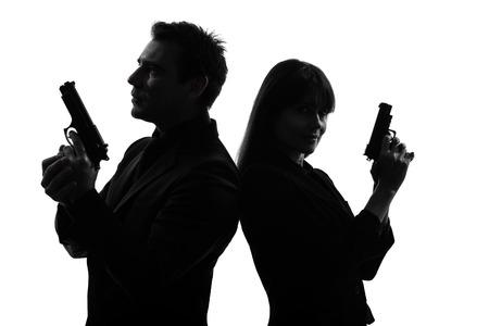 hombre disparando: hombre mujer pareja criminal detective agente secreto con el arma en la silueta del estudio aislada en el fondo blanco