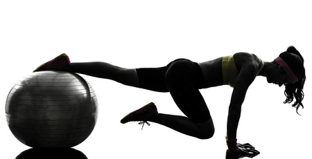 one woman exercising fitness workout plank position on fitness ball in silhouette on white background photo