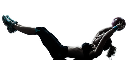 one  woman exercising fitness ball workout crunches in silhouette studio isolated on white background