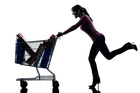 one  woman with full shopping cart in silhouette studio isolated on white background photo