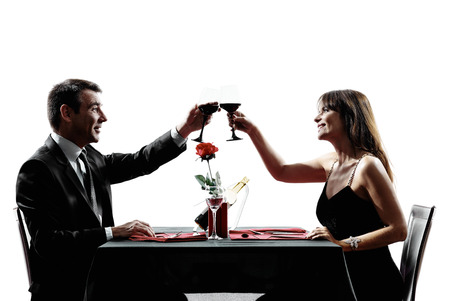 wine and dine: couples lovers dinning drinking wine in silhouettes on white background Stock Photo
