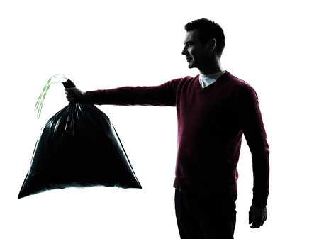man dumping garbage bag in silhouettes on white background photo