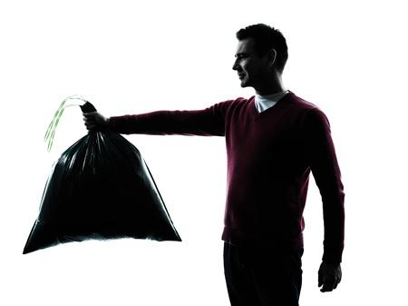 dumping: man dumping garbage bag in silhouettes on white background