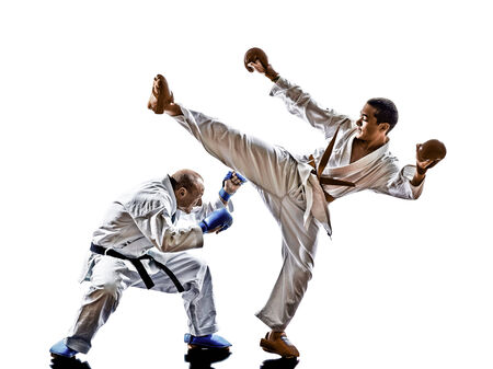 fighting arts: two karate men sensei and teenager student fighters fighting protections isolated on white background