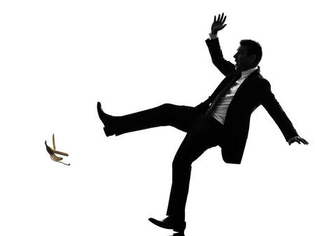 hombre cayendose: un caucásico desafortunado hombre de negocios sin preocupaciones en silueta sobre fondo blanco Foto de archivo